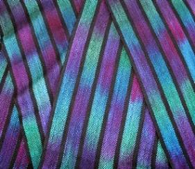 A handwoven painted warp scarf closeup